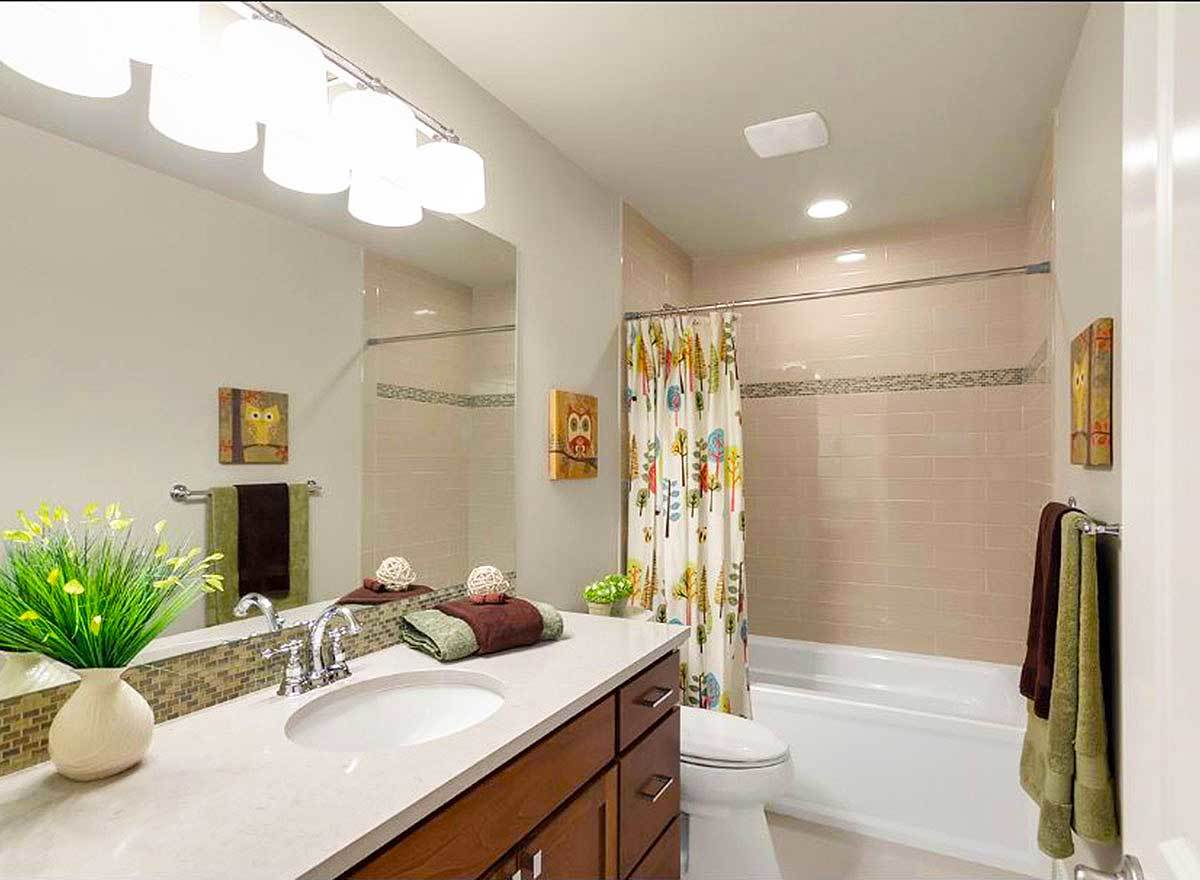 Another bathroom offering the same amenities. It has gray walls and a matching regular ceiling.