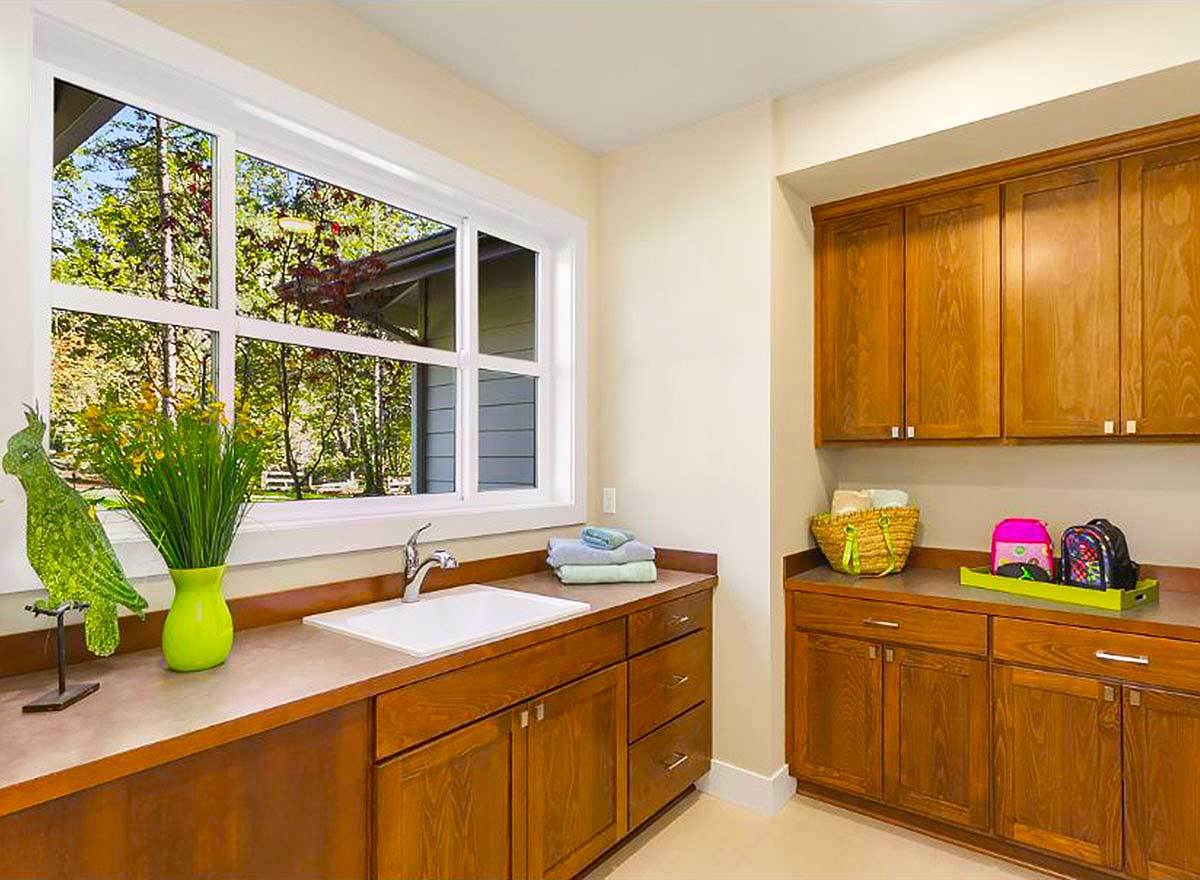 The laundry room is filled with rich wood cabinets and an undermount sink fixed under the white framed window.