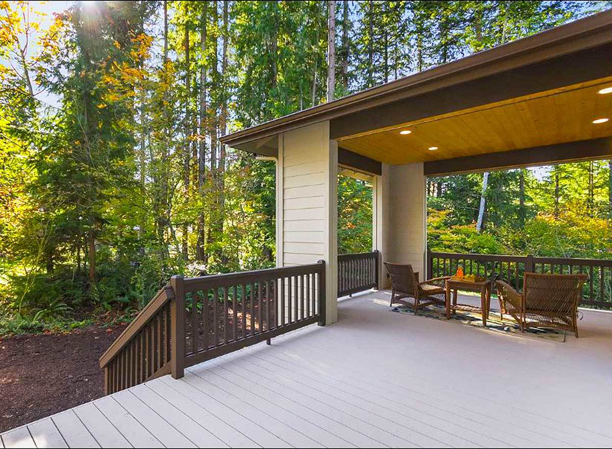 A half-covered deck with a staircase leading down the lush backyard.