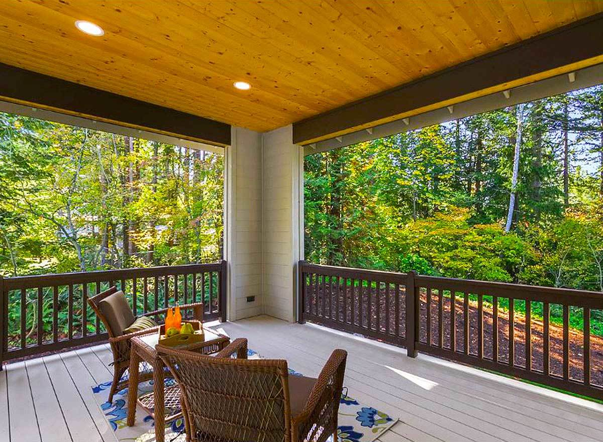 The covered deck is furnished with wicker cushioned armchairs, a matching side table, and a floral rug that lays on the wide plank flooring.