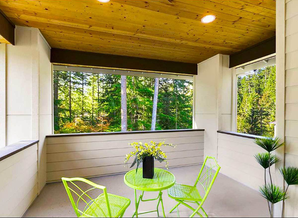 Neon green chairs and a round side table stand out against the shiplap walls and concrete flooring of this deck.