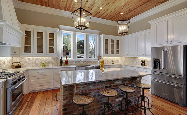 The kitchen has a hardwood flooring and a matching wood-paneled ceiling mounted with lantern pendants and recessed lights.
