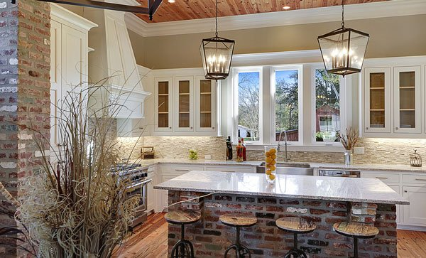 White cabinets and stainless steel appliances surround the brick island that's lined with round bar stools.