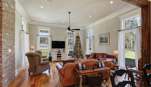 Family room with brown leather sofas, skirted wingback chairs, and a flat-screen TV mounted above the white console table.