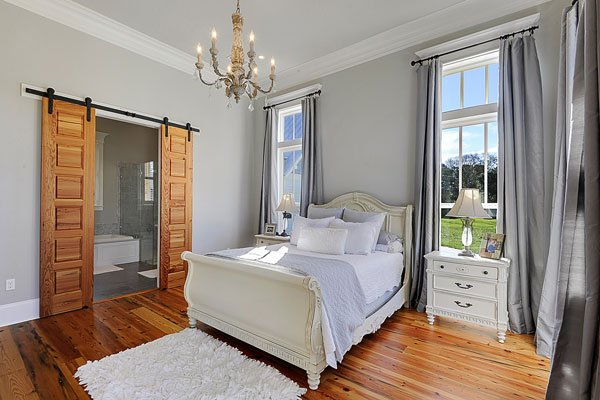 The primary bedroom has light gray walls and rich hardwood flooring that matches the pocket doors leading to the bathroom.