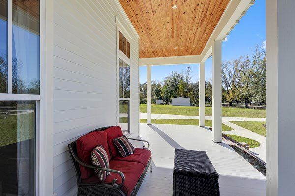 The covered porch is filled with a wicker ottoman and a red cushioned bench that stands out against the white exterior siding.