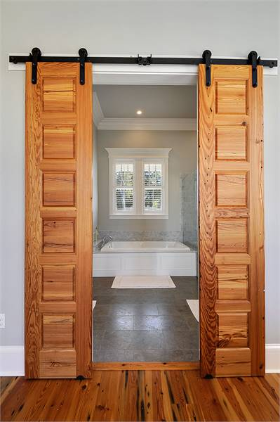 Stylish pocket doors in natural wood lead to the primary bathroom.