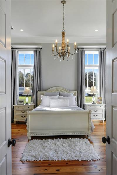 A white double door opens to the primary bedroom with gray walls and rich hardwood flooring topped with a shaggy rug.