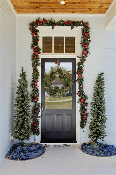 Home's dark wood front door against the white exterior siding adorned with holiday decors.