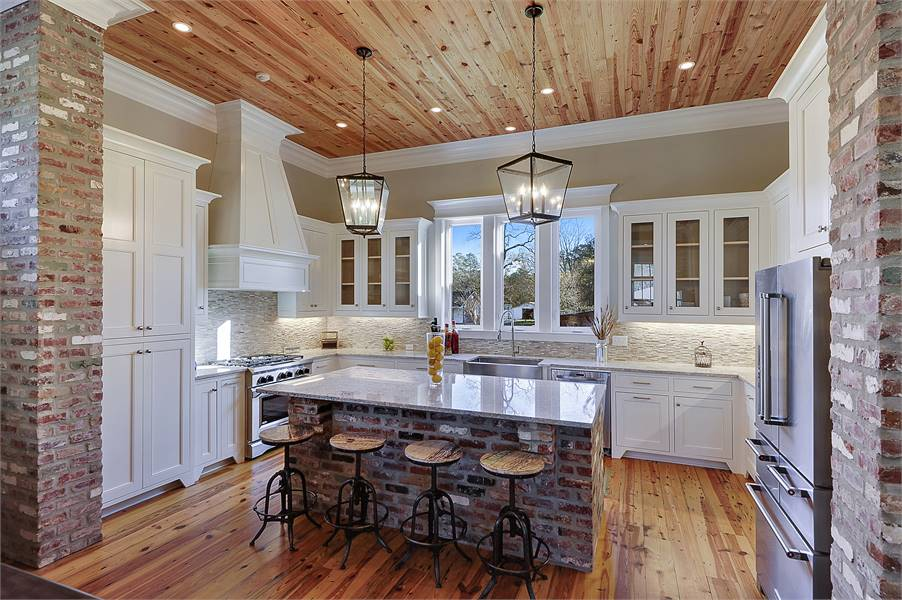 The kitchen has beige walls and hardwood flooring that matches the wood-paneled ceiling.
