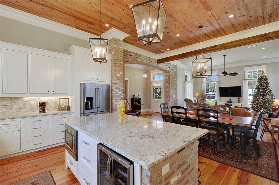 The center island clad in stone bricks is fitted with stainless steel appliances and white pull-out drawers.