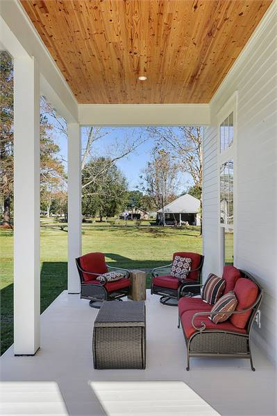 Wicker coffee table along with matching chairs topped with red cushions fill the front porch.