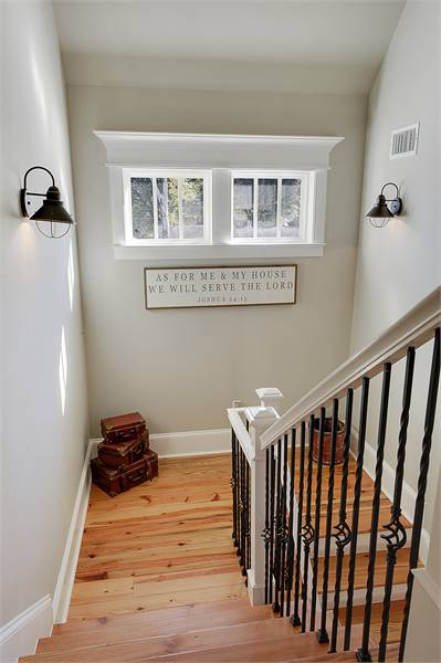 Staircase landing well-lit by vintage sconces along with natural light from the white-framed windows.