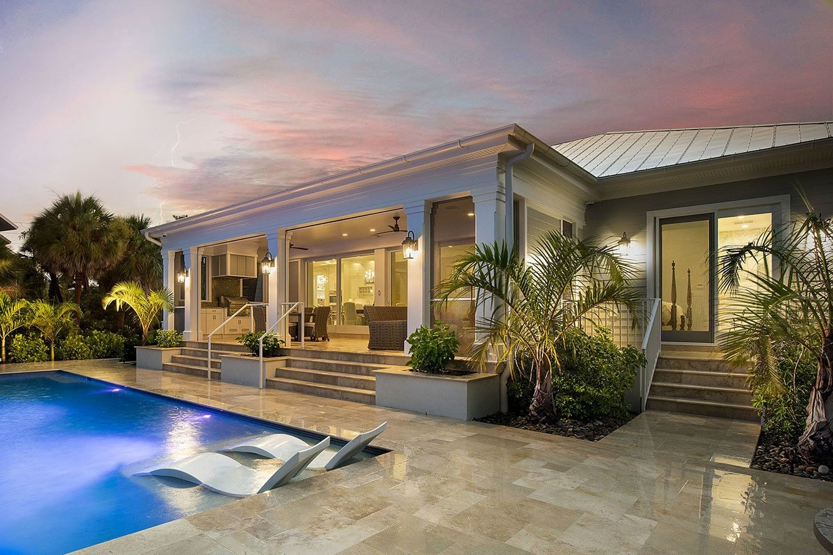 Rear exterior view showing the lanai filled with outdoor living and kitchen. There's also a pool complemented with sleek loungers.