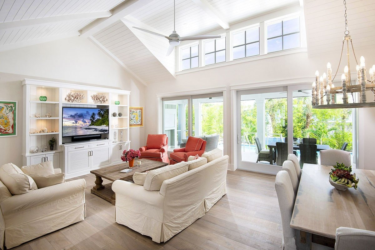 The living room has wide plank flooring and a shiplap vaulted ceiling with exposed wood beams and a hanging fan.