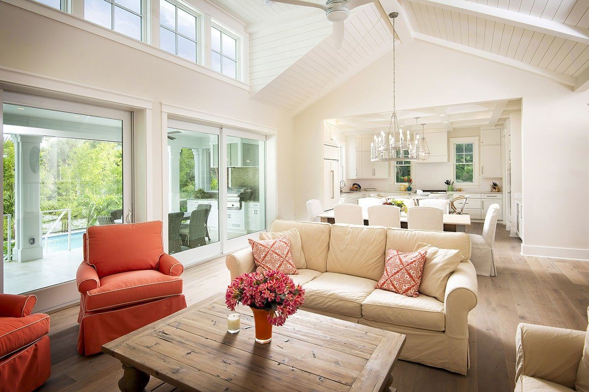 Beige and red cushioned seats along with a wooden coffee table complete the living room.
