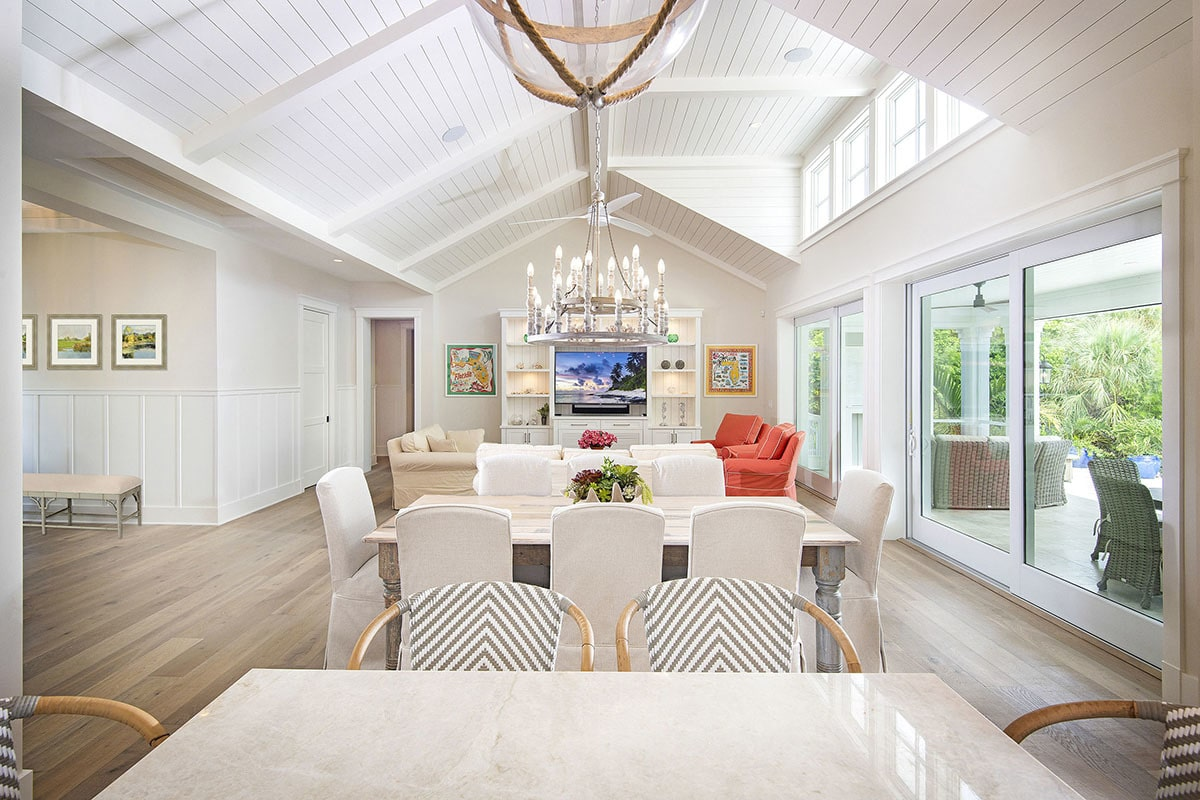 The dining room offers white skirted chairs and a rustic dining table sitting under the round candle chandelier.