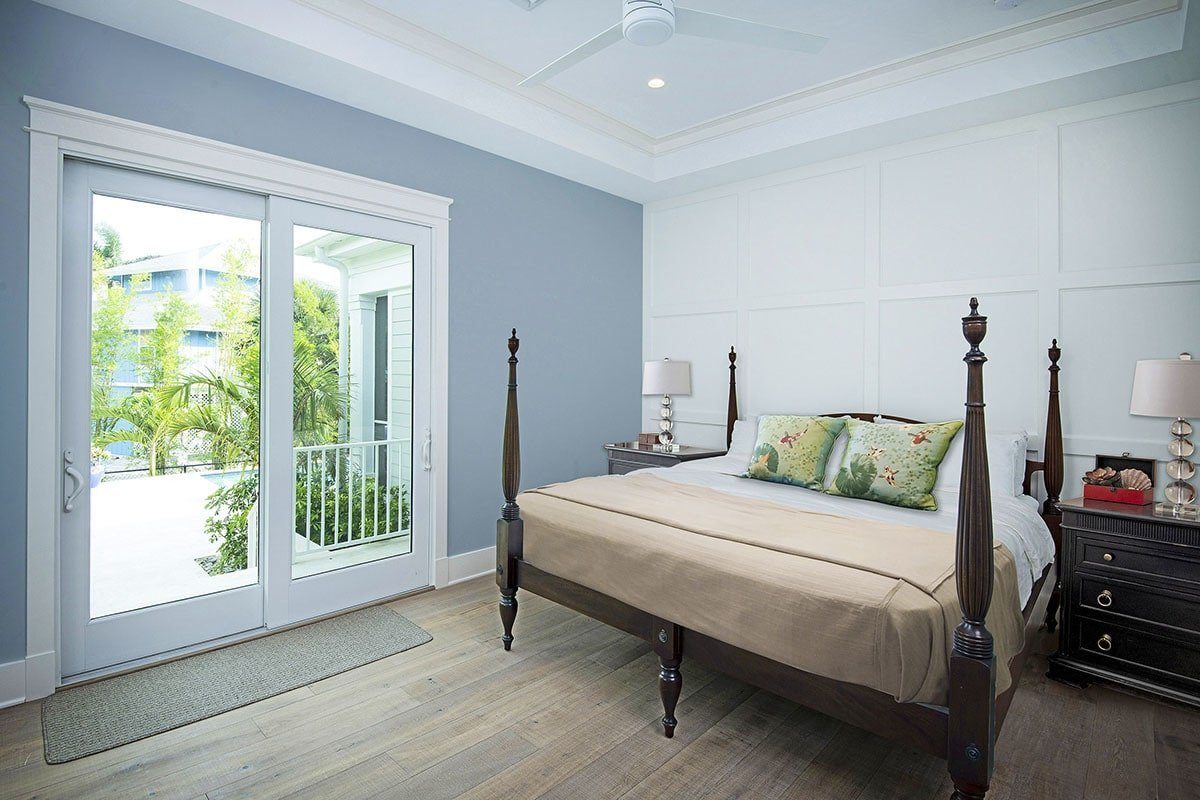 Master bedroom with a tray ceiling and a private balcony accessible through the sliding glass doors.