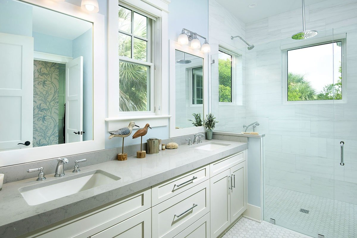 The master bathroom has a walk-in shower and dual sink vanity paired with white framed mirrors and chrome sconces.