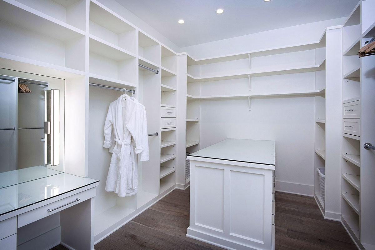 Walk-in closet with glass top vanity and a center island matching with the built-in shelves.Walk-in closet with glass top vanity and a center island matching with the built-in shelves.