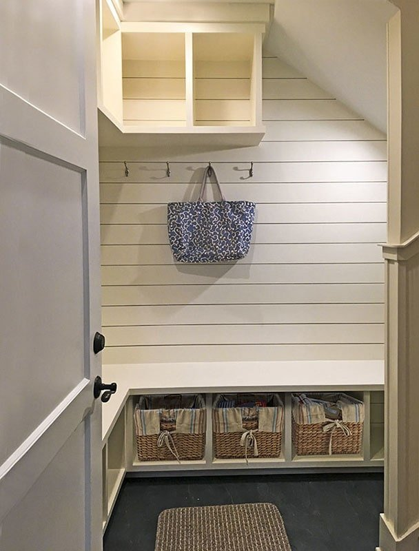 Mudroom with floating shelves, coat pegs, and a built-in bench filled with storage baskets.