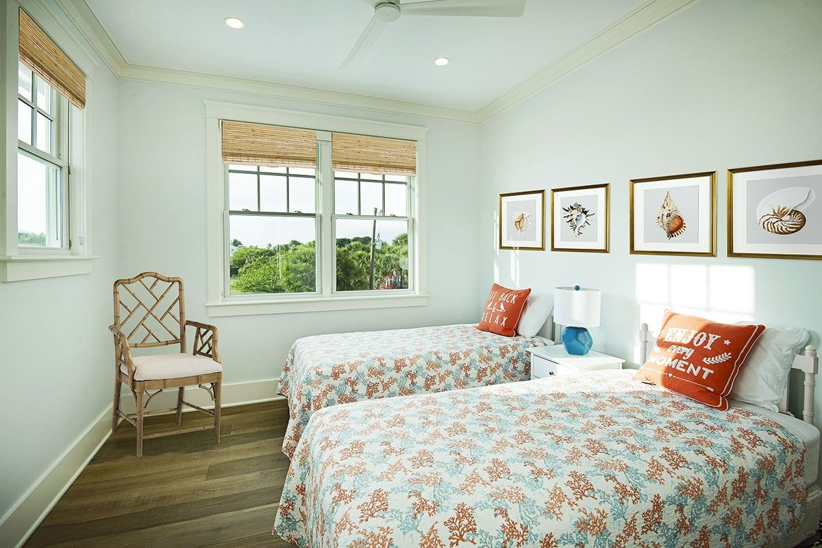 This bedroom has a wooden chair, two beds, and framed artworks adorning the light blue walls.