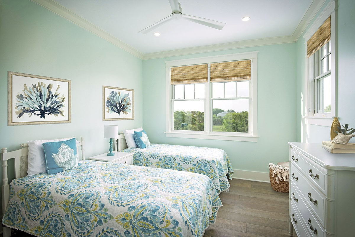Another bedroom with a white dresser and two beds flanking the white nightstand topped with a drum table lamp.