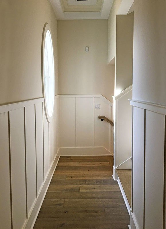 This hallway has natural hardwood flooring and beige walls graced with white beadboard and a large round window.