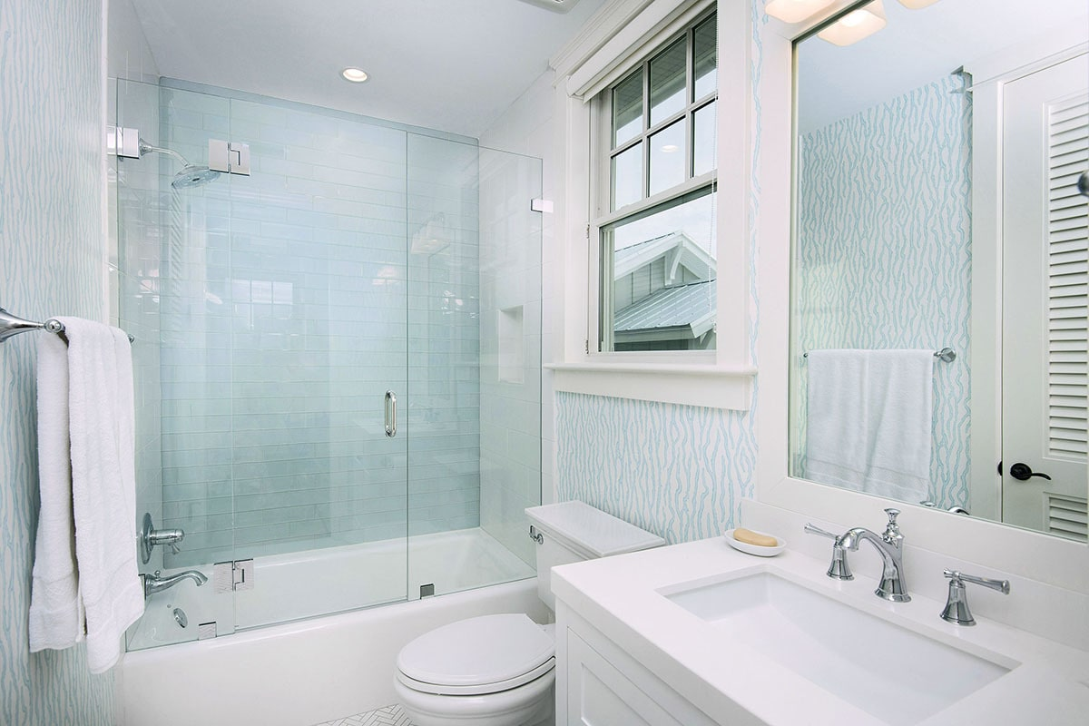 This bathroom is equipped with a washstand, a toilet, and a tub and shower combo enclosed in frameless glass.