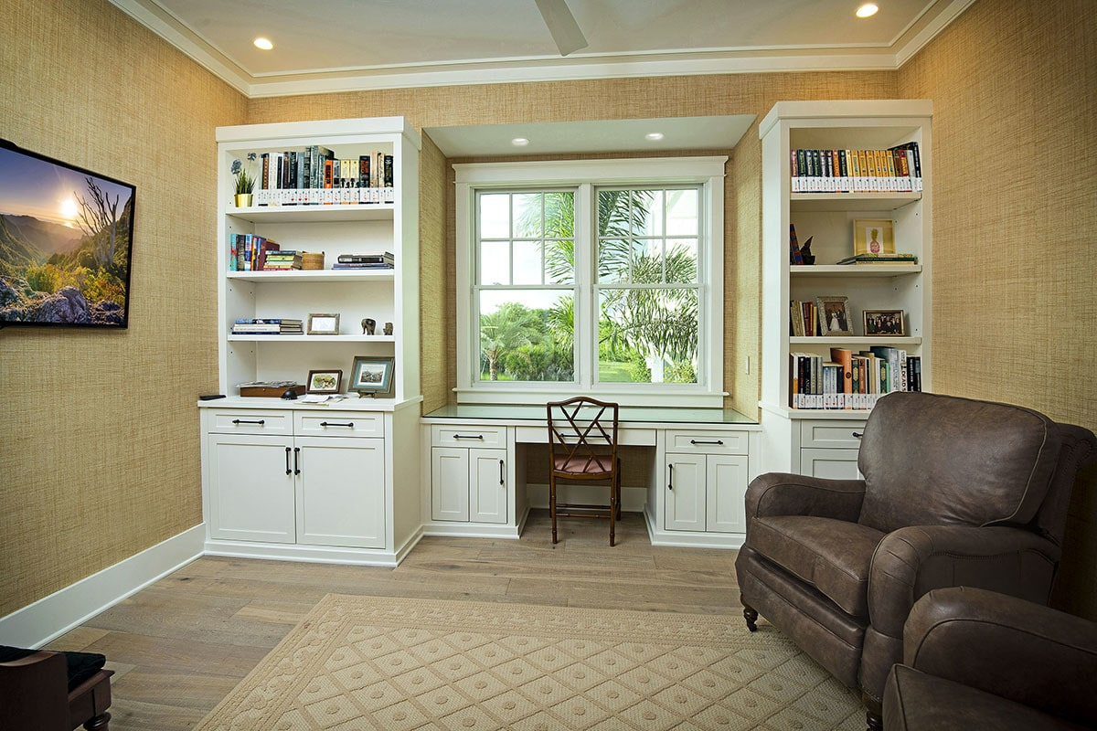 Study with built-in desk and cabinets along with brown leather armchairs facing the wall-mounted TV.