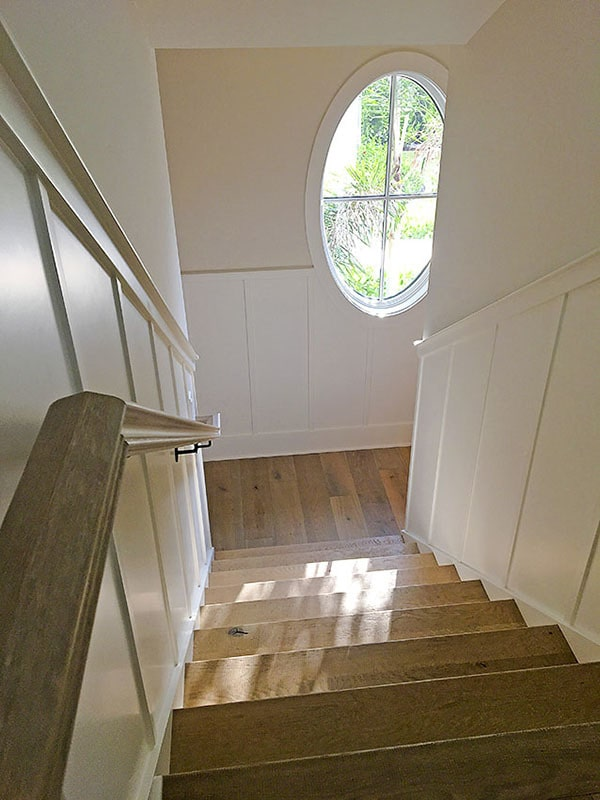 A wooden staircase with a matching handrail leading down the mudroom.