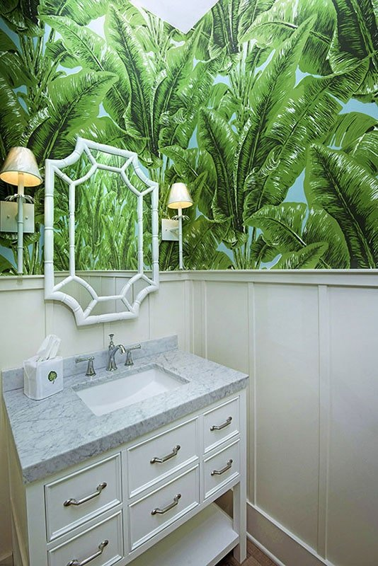 Powder room with a marble top vanity and a stylish mirror fixed against the foliage wallpaper.