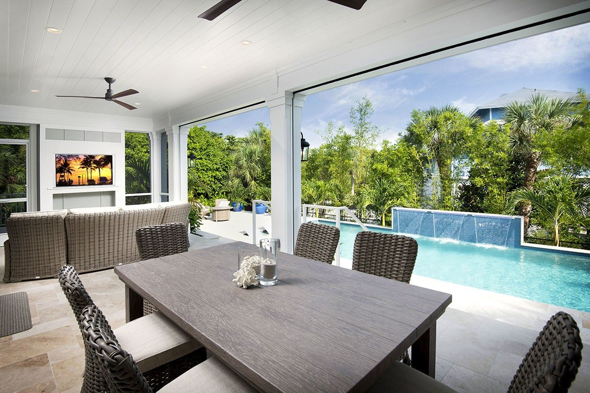 Covered lanai with wicker seats and a wooden table sitting on a limestone flooring.