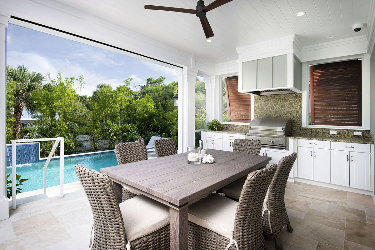 The opposite view shows the outdoor kitchen with white cabinets and a elegant granite countertops.
