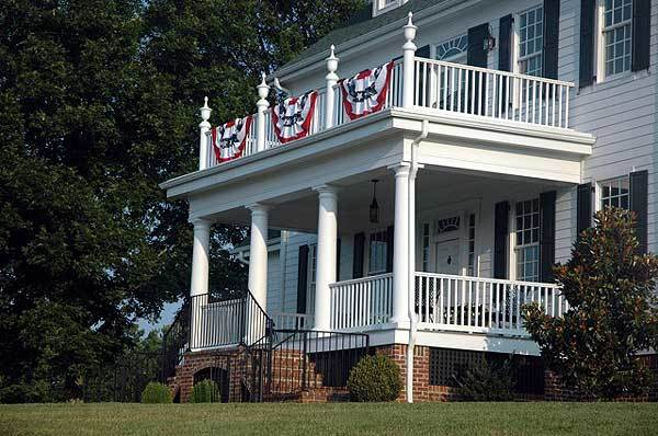 Covered front porch lined with exterior columns and complemented with a brick stoop enclosed in wrought iron railings.