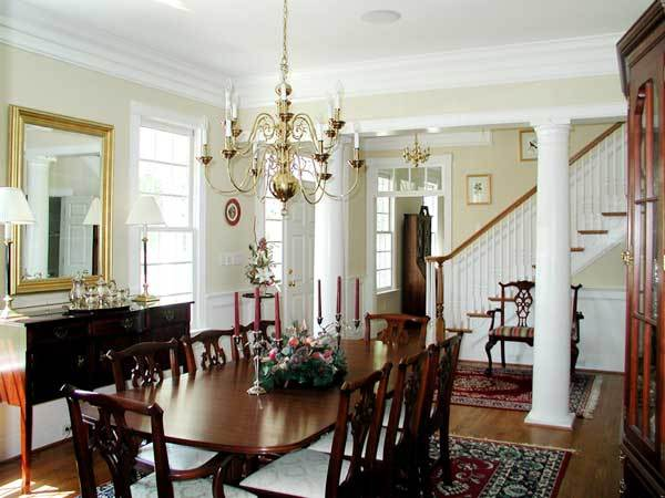 The formal dining room is illuminated with a gilded candle chandelier that hangs over the wooden dining set.