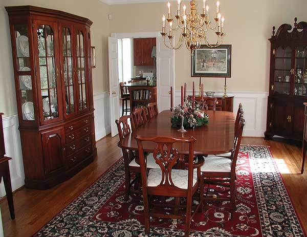 Dark wood display cabinets and a red area rug over the hardwood flooring complete the dining room.