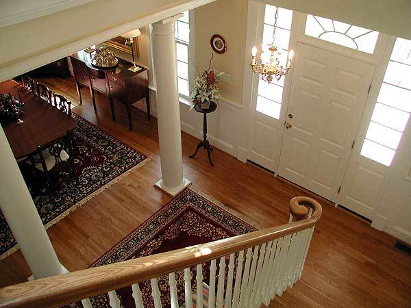 View of the foyer from the staircase showing the candle chandelier and a white entry door surrounded with glass panels.