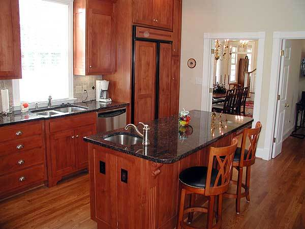 A focused shot at the kitchen's island with elegant black granite countertop and round cushioned stools.
