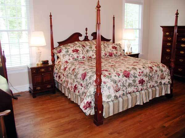 The primary bedroom features a four-poster bed flanked with dark wood nightstands and decorative table lamps.