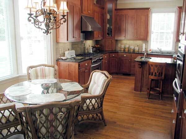 Breakfast nook across the kitchen with stripe cushioned chairs and a round glass dining table under the ornate chandelier.