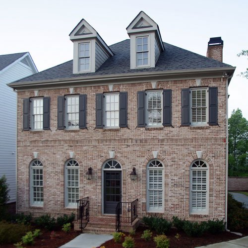 Home's facade with brick cladding, decorative shutters, arched windows, and front door, and charming dormers sitting on top of the hipped roof.