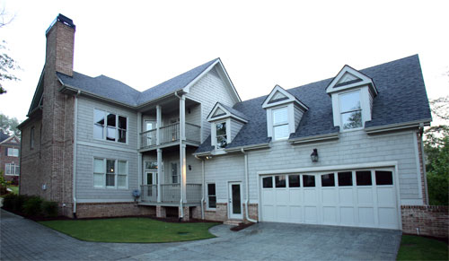 The rear exterior view shows the two-car garage and covered balconies lined with slim white columns.