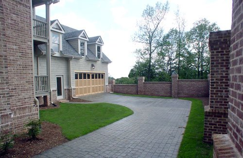 A brick driveway nestled in between the lush green lawns leading to the two-car garage.