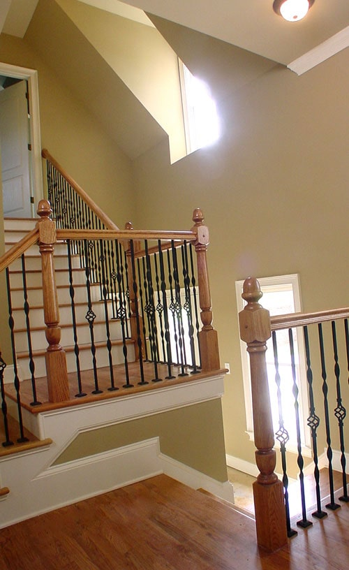 The traditional staircase has natural wooden steps and elaborate railings composed of wooden posts and ornate wrought iron spindles.