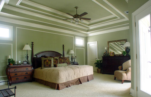 The primary bedroom has dark wood furnishings and a stunning step ceiling matching with the sage green walls.