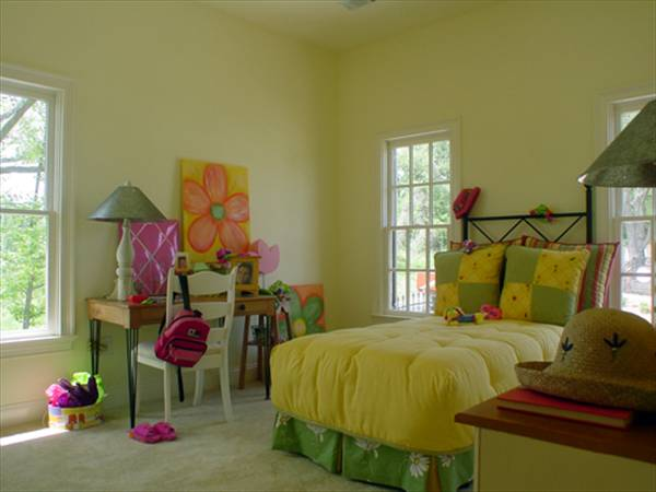 Kid's bedroom with beige carpet flooring and yellow walls fitted with white framed windows.