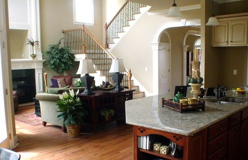 View of the family room from the kitchen's peninsula with wooden shelving and granite countertop.