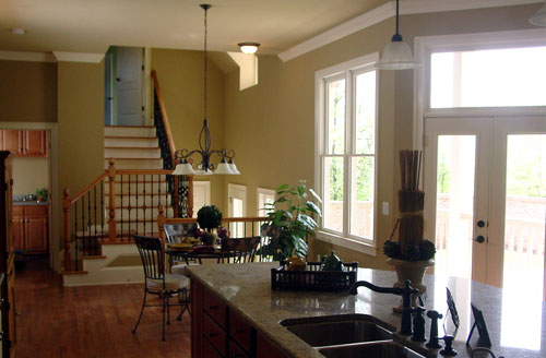 The center island across the breakfast nook is topped with a double bowl sink and a granite countertop.
