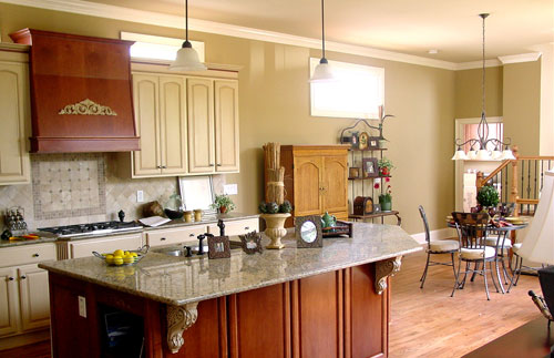 A farther view of the kitchen shows the cream cabinetry and a wooden vent hood that matches the island bar.